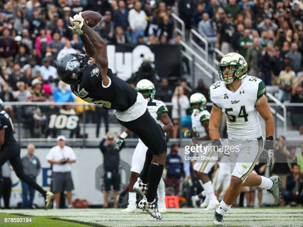 Dredrick Snelson of the UCF Knights catches a pass for a touchdown as Nico Sawtelle of the South Florida Bulls looks on in the first quarter at...
