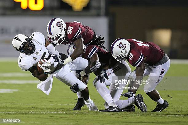 Dredrick Snelson of the UCF Knights gets tackled by Bruce Johnson and Devondre Powell of the South Carolina State Bulldogs during a NCAA football...