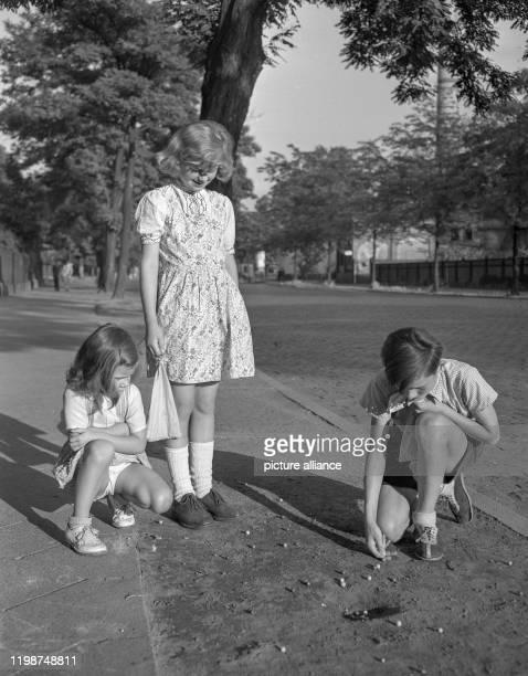Drei Kinder beim Spiel mit Murmeln auf einem ungepflasterten Gehweg Aufnahme von 1951