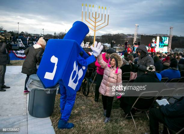 Dreidel Man greets a young attendee during the annual National Menorah Lighting in celebration of Hanukkah on the Ellipse near the White House...