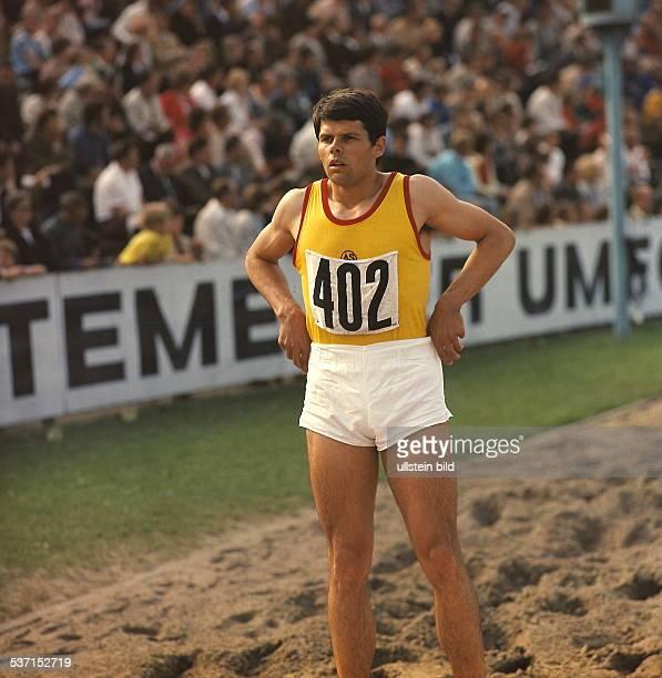 Dreispringer DDR steht bei einem Wettkampf im Sand der Grube oJ