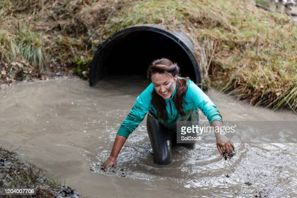 drenched woman coming out of water tunnel on outside obstacle course - caucasian appearance stock pictures, royalty-free photos & images
