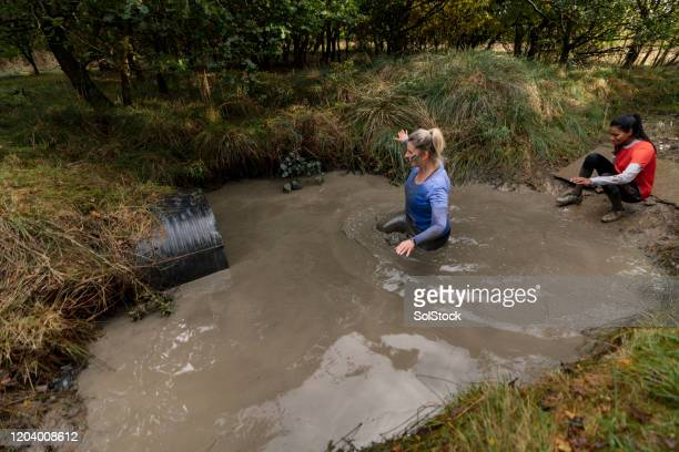 drenched woman wading to tunnel in pool of standing water - wading stock pictures, royalty-free photos & images