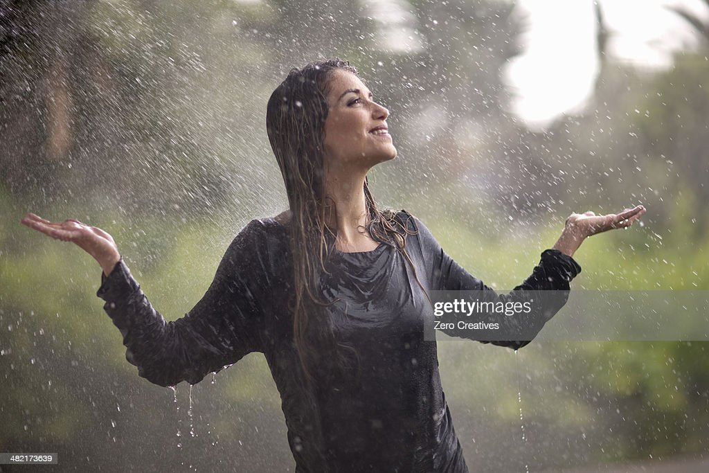 Drenched young woman with arms open in rainy park : Stock Photo