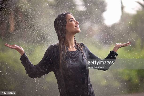 drenched young woman with arms open in rainy park - nass stock-fotos und bilder