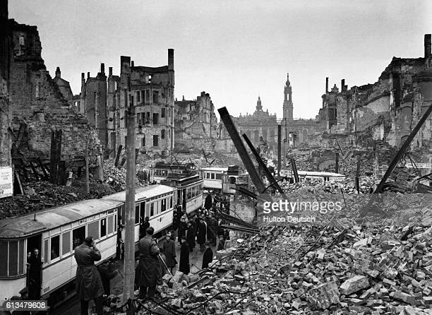 Dresden citizens in the Soviet sector of Germany attempt to get on trams amidst the ruins and chaos remaining since the city was reduced to ruins by...