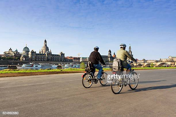 dresden skyline with two passing cyclists - エルベ川 ストックフォトと画像