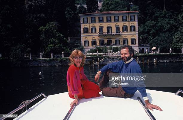 Dress designer Gianni Versace and Lalla Spagnol on a motor launch in front of his 17th century villa on Lake Como June 1983