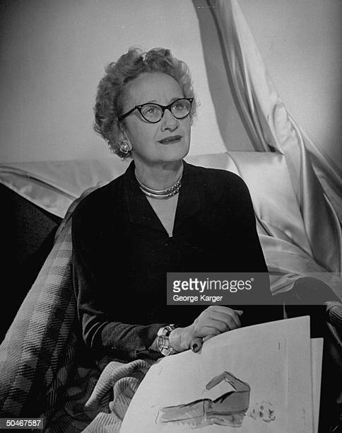 Dress designer Hattie Carnegie holding sketches in hand sitting amid bolts of material