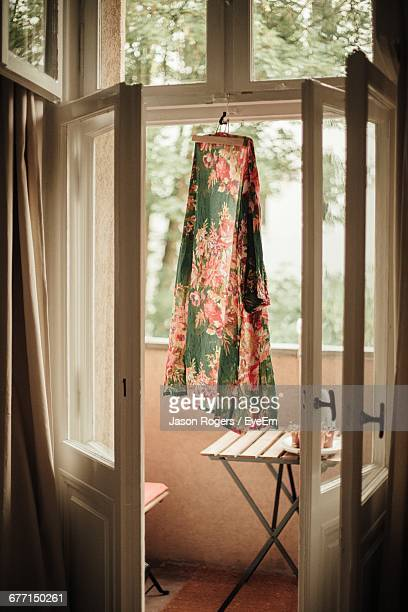 dress drying on doorway of balcony - floral pattern dress stock pictures, royalty-free photos & images
