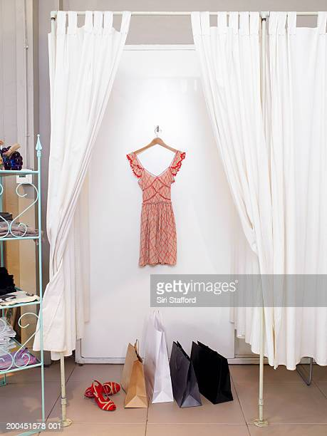 Dress hanging in dressing room, shopping bags on floor