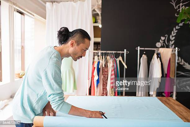dress maker cutting fabric - jgalione stock pictures, royalty-free photos & images