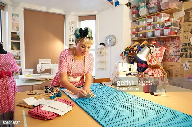 Dress maker preparing material in workshop.