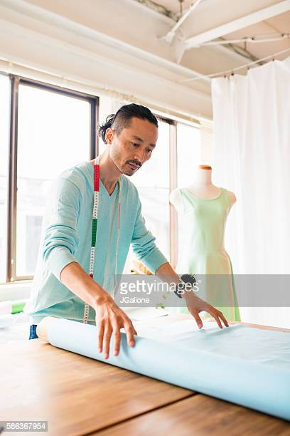 Dress maker rolling out fabric