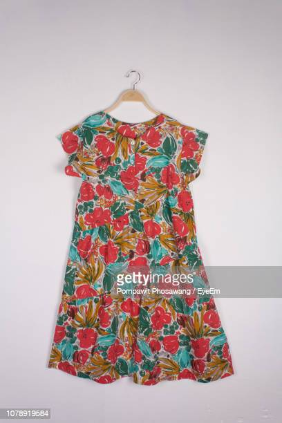 dress on coathanger against white background - floral pattern dress stock pictures, royalty-free photos & images