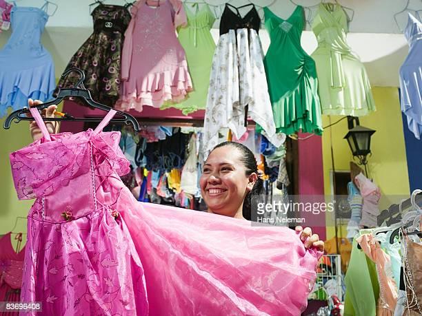 Dress shop owner displaying her wares