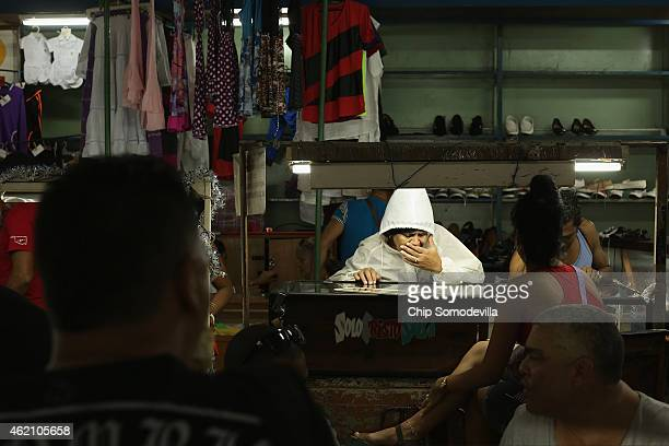 Dressed against the rain a woman looks at a small jewelry counter in an indoor marketplace in the Habana Vieja neighborhood January 24 2015 in Havana...