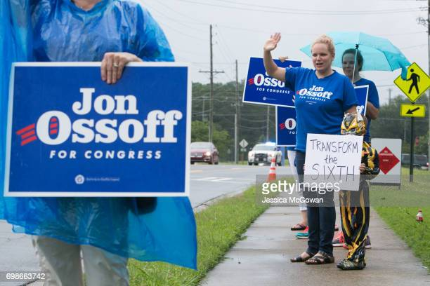Dressed as a Transformer character Malcolm Nichols stands with Melissa Cochran campaigning for Democratic candidate Jon Ossoff outside of the East...