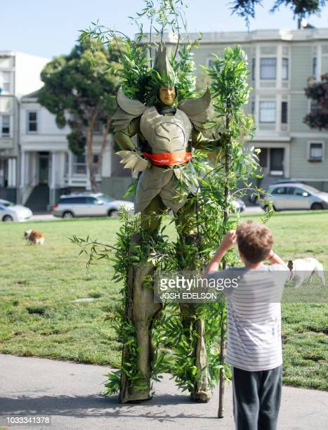Dressed as a tree on stilts Jodi Power stands while a boy takes her photo during the Global Climate Action Summit in San Francisco California on...