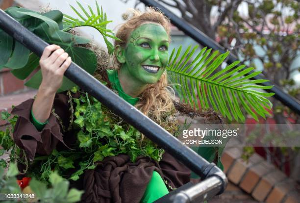 Dressed as a tree on stilts Krysta Cook rests on a residential staircase during the Global Climate Action Summit in San Francisco California on...