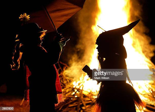 Dressed as a witch Leigh Kosega and Zabell Carstens dressed as Mary Poppins stand near a bon fire October 25 2003 in Huntingtown Maryland With the...