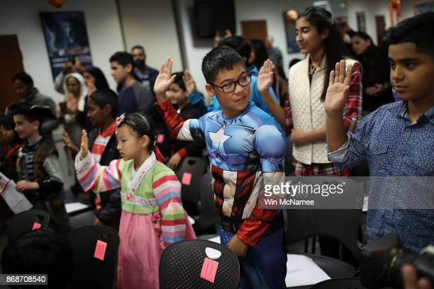 Dressed as Captain America Caleb Lee Burton from the Republic of Korea takes the oath of US citizenship with other children during a Halloweenthemed...