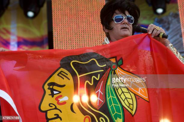 Dressed as Elvis Presley actor Bill Murray holds a Chicago Blackhawks hockey team banner as he performs onstage at Eric Clapton's Crossroads Guitar...