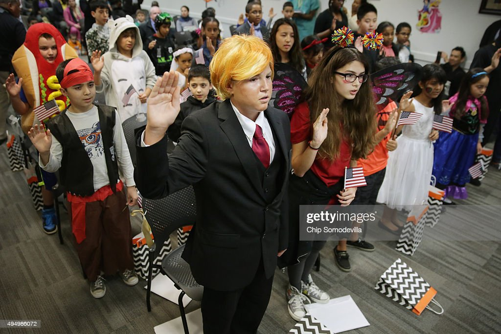 Dressed as Republican presidential candidate Donald Trump, 13-year-old Razvan Godja (C) and 26 other children wear Halloween costumes as they take the Oath of Allegiance during their naturalization ceremony at the U.S. Citizen and Immigration Services Washington Field Office October 30, 2015 in Washington, DC. Godja, who was born in Romania, and the other children became some of the United States' youngest and newest citizens on the day before heading out for the American tradition of trick-or-treating.