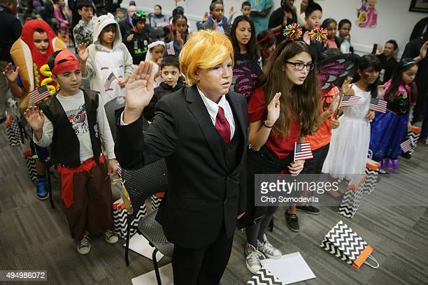 Dressed as Republican presidential candidate Donald Trump 13yearold Razvan Godja and 26 other children wear Halloween costumes as they take the Oath...