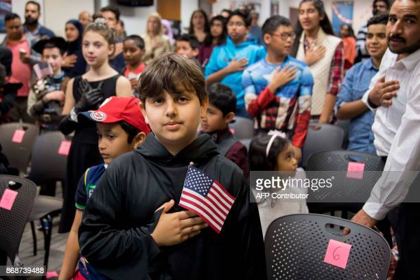 Dressed as the Grim Reaper Shabir Safi from Afghanistan says the Pledge of Allegiance during a US citizenship special Halloweenthemed ceremony at the...