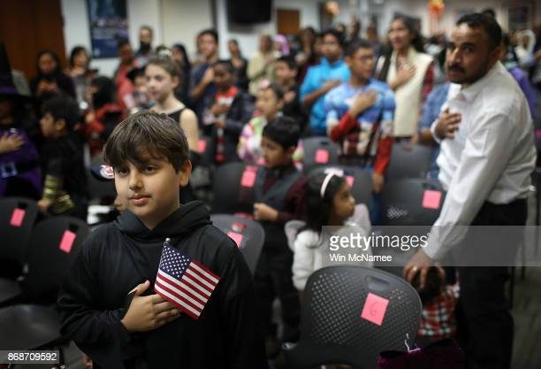 Dressed as the Grim Reaper Shabir Safi from Afghanistan takes the oath of US citizenship with other children during a Halloweenthemed citizenship...