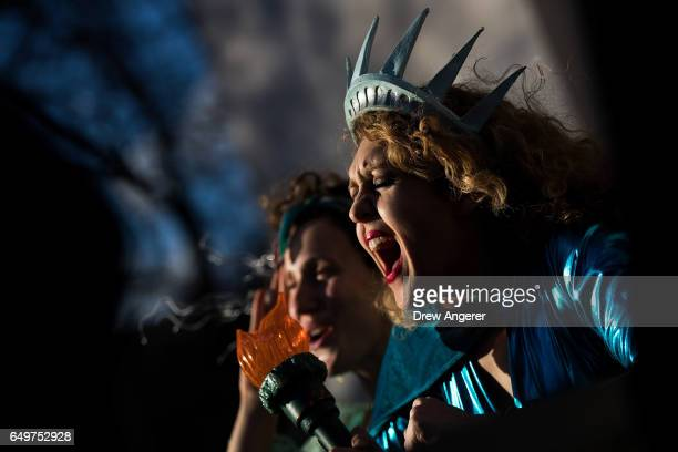 Dressed as the Statue of Liberty Sonia Sheron cheers as she attends a rally to mark International Women's Day in Washington Square Park March 8 2017...