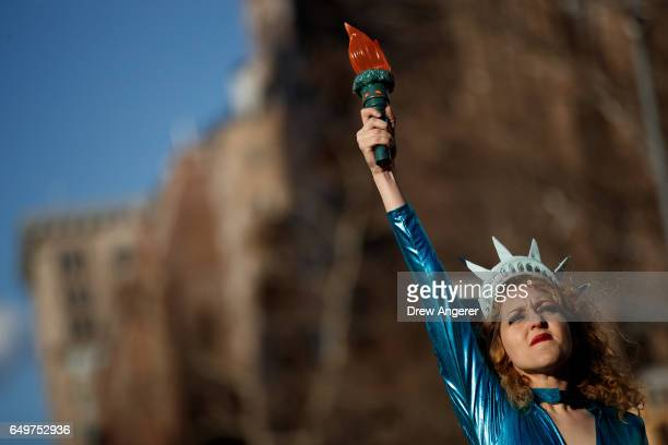 Dressed as the Statue of Liberty Sonia Sheron performs onstage during a rally to mark International Women's Day in Washington Square Park March 8...