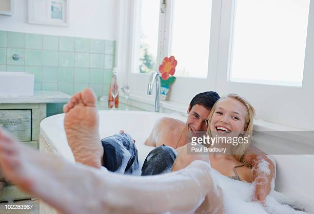 dressed couple in bubble bath - freaky couples stockfoto's en -beelden