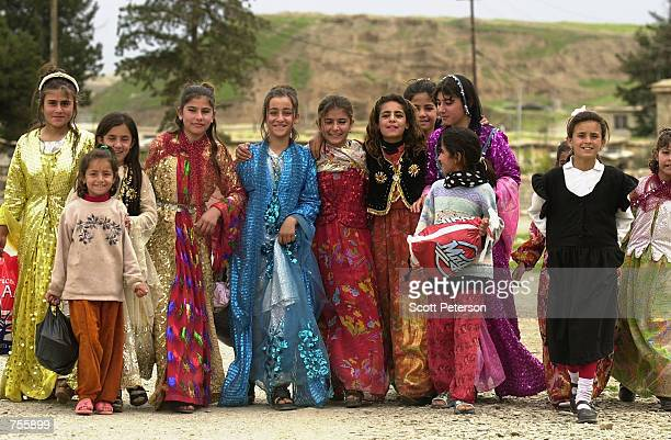 """Dressed for festivities, Kurdish girls walk to a countryside picnic March 28, 2002 in Kanipanka, part of the northern Iraq """"safe haven"""" controlled by..."""
