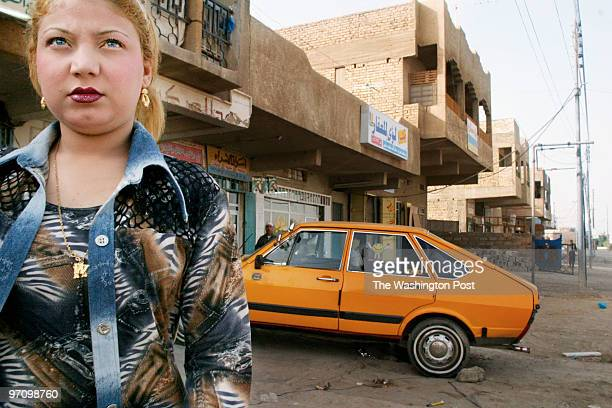 Dressed for her job Halla Muhammed Maarouf walks down the street outside her Baghdad apartment Western clothes dyed blond hair and blue eyed contacts...