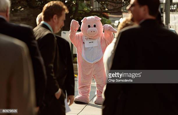 Dressed in a pig costume, a member of the Laborers' International Union of North America rallies outside the National Association of Homebuilders...