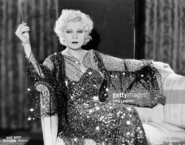 Dressed in a sequinned gown, Mae West lounges with a cigarette in her first screen role as Maudie in 'Night After Night', directed by Archie Mayo.