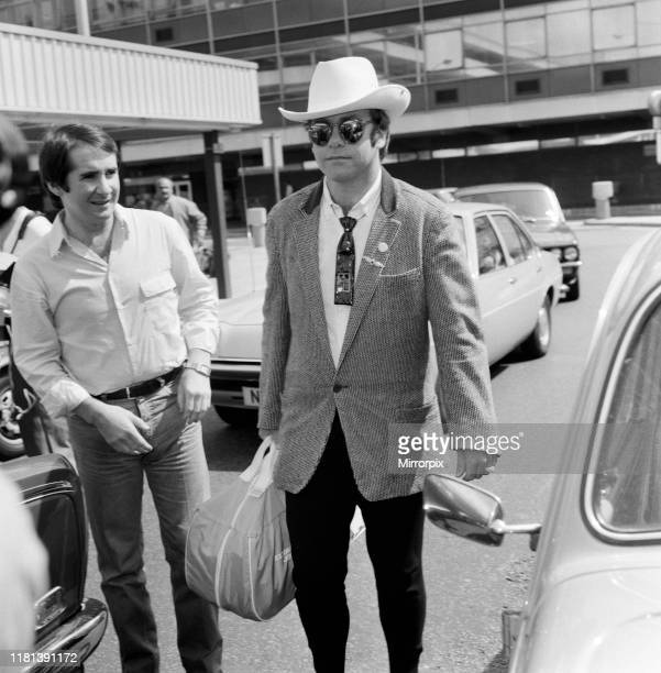 Dressed in a stetson hat Elton John leaves Heathrow Airport for America On the left is John Reid Elton's manager 10th August 1980