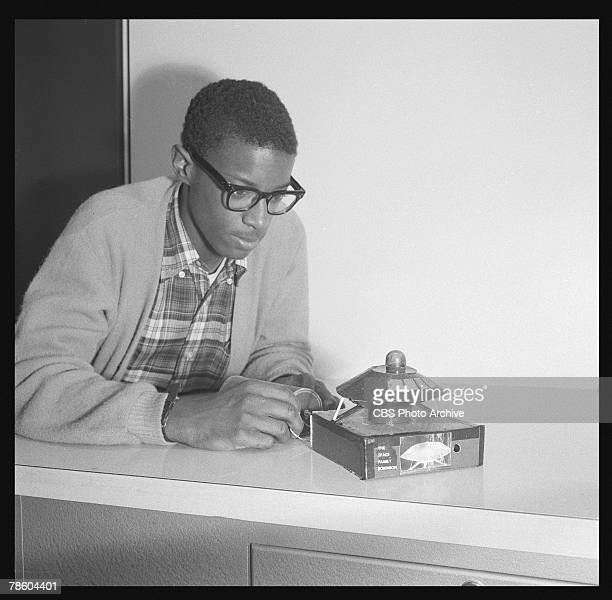 Dressed in a sweater and blackframed eyeglasses Herbert Wells attaches electrical leads from a battery to a homemade model of the Jupiter 2...