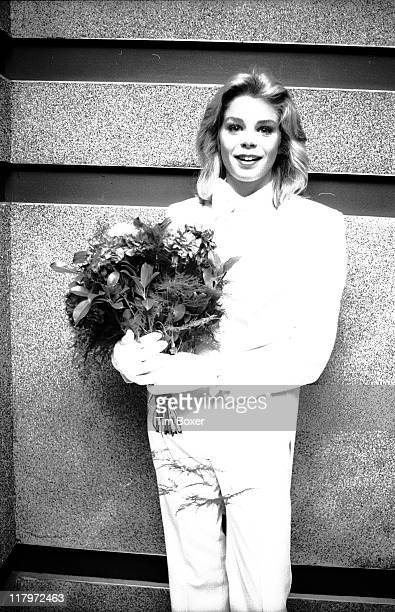 Dressed in a white tuxedo American actress and former Playboy cover girl Kristine DeBell holds a bouquet of flowers as she attends the premiere of...