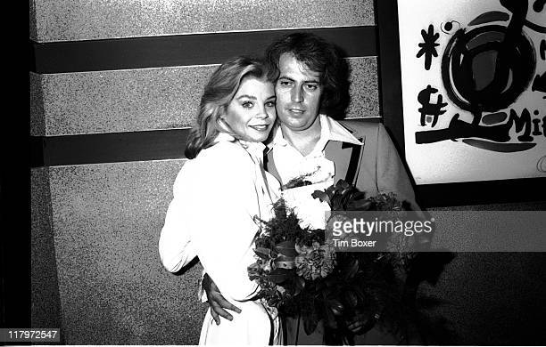 Dressed in a white tuxedo American actress and former Playboy cover girl Kristine DeBell holds a bouquet of flowers as she poses with film producer...