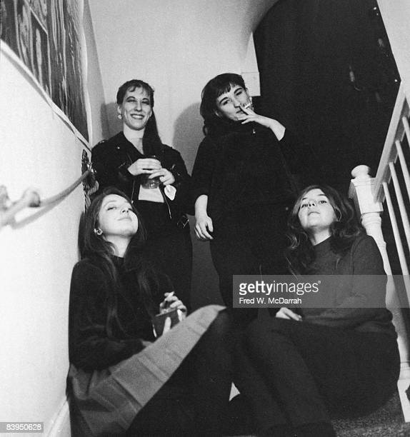 Dressed in black female attendees at a 'RentaBeatnik' party smoke at the top of a staircase in a townhouse in Sniffen Court New York New York April 1...