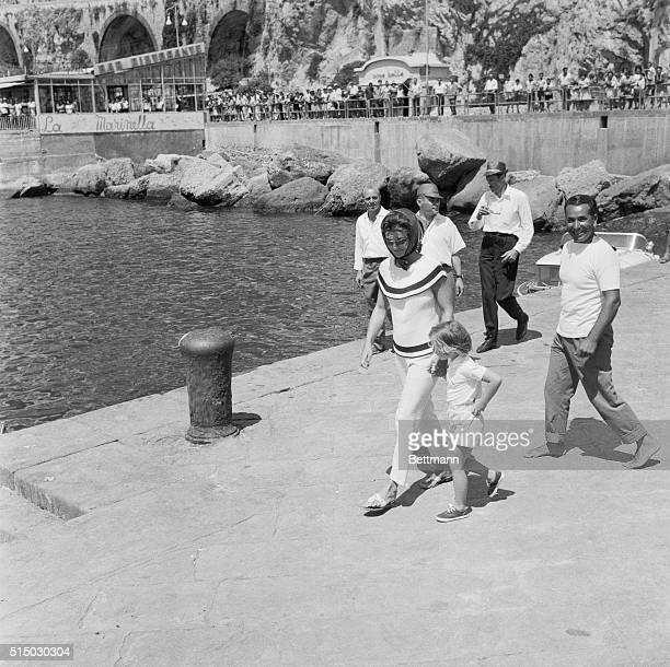 Dressed in capri pants and with a mantilla covering her hair Mrs Jacqueline Kennedy and her daughter Caroline stroll hand in hand along the pier at...