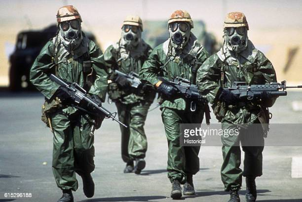 Dressed in rain suits gloves and M17A1 protective masks four soldiers from the 82nd Airborne Division walk around their camp to acclimate their...