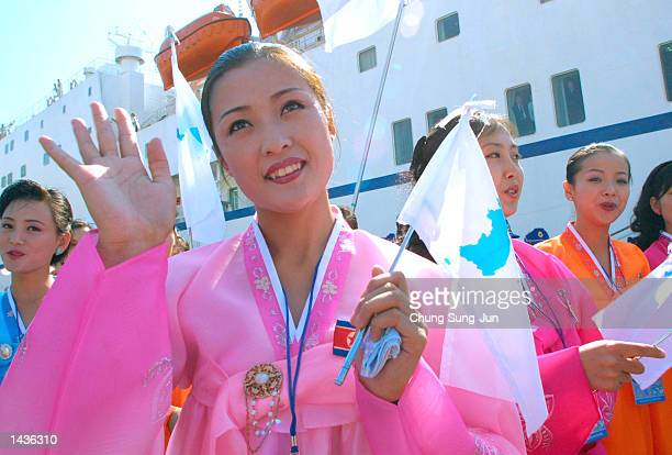 Dressed in colorful traditional robes a North Korean woman waves a Unification flag upon her arrival at Dadaepo port September 28 2002 in Busan South...