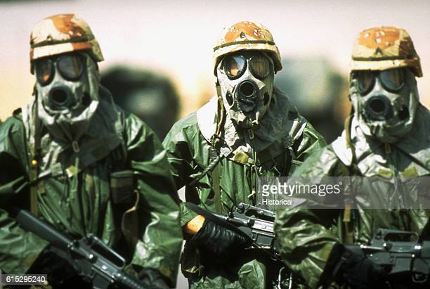 Dressed in rain suits, gloves and M-17A1 protective masks, three soldiers from the 82nd Airborne Division walk around their camp to acclimate their...