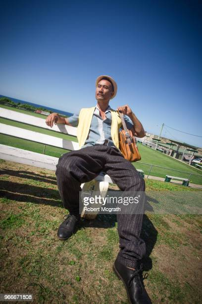 Dressed in retro fashions, a young Australian-Chinese man slouches on a park bench, outside a bowling club, overlooking the ocean, on a hot, sunny summer's afternoon.
