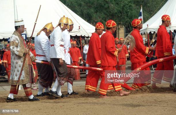 Dressed in royal ceremonial costumes the official handlers of the royal cows walk alongside their charges as they ritually plough the Royal Field The...