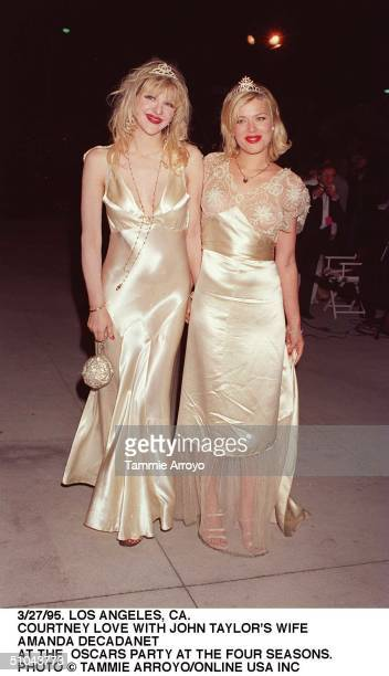 Dressed in similar silver evening gowns and tiaras American musician and actress Courtney Love and British actress and model Amanda de Cadenet pose...